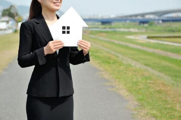 紙でできた家を持つ黒スーツの女性