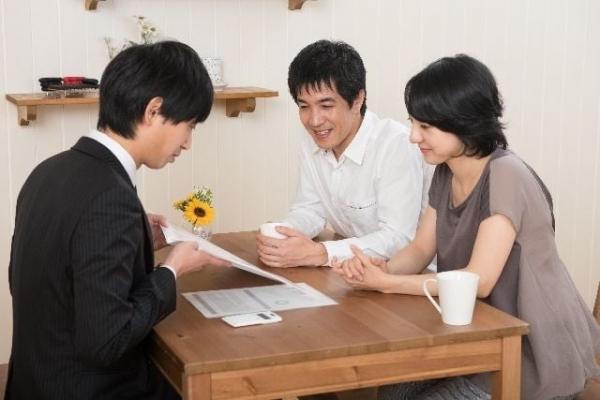 打ち合わせをする夫婦と営業マン